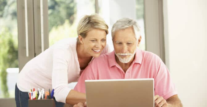 Adult Daughter And Senior Father Using Laptop At Home