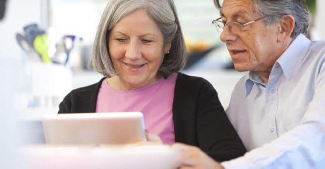 retired couple looking at iPad together